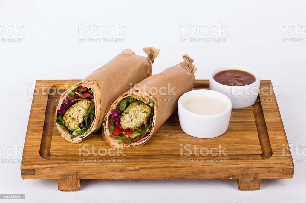 vegetarian falafel shawarma on the board with sauce isolated stock photo