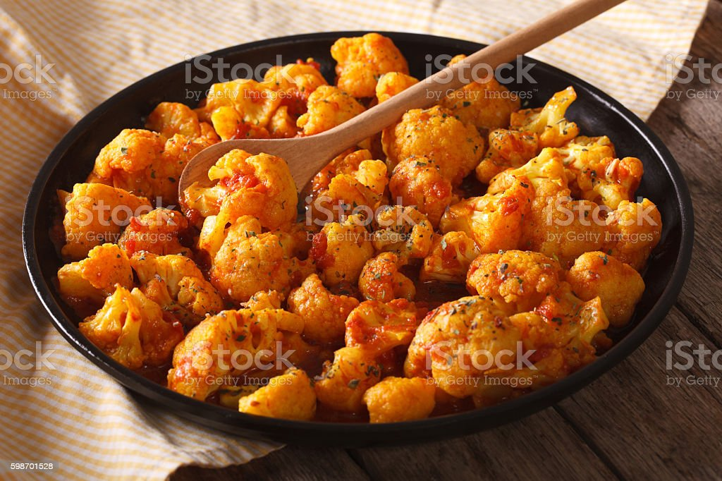 Vegetarian food: Cauliflower in curry sauce close-up. Horizontal stock photo