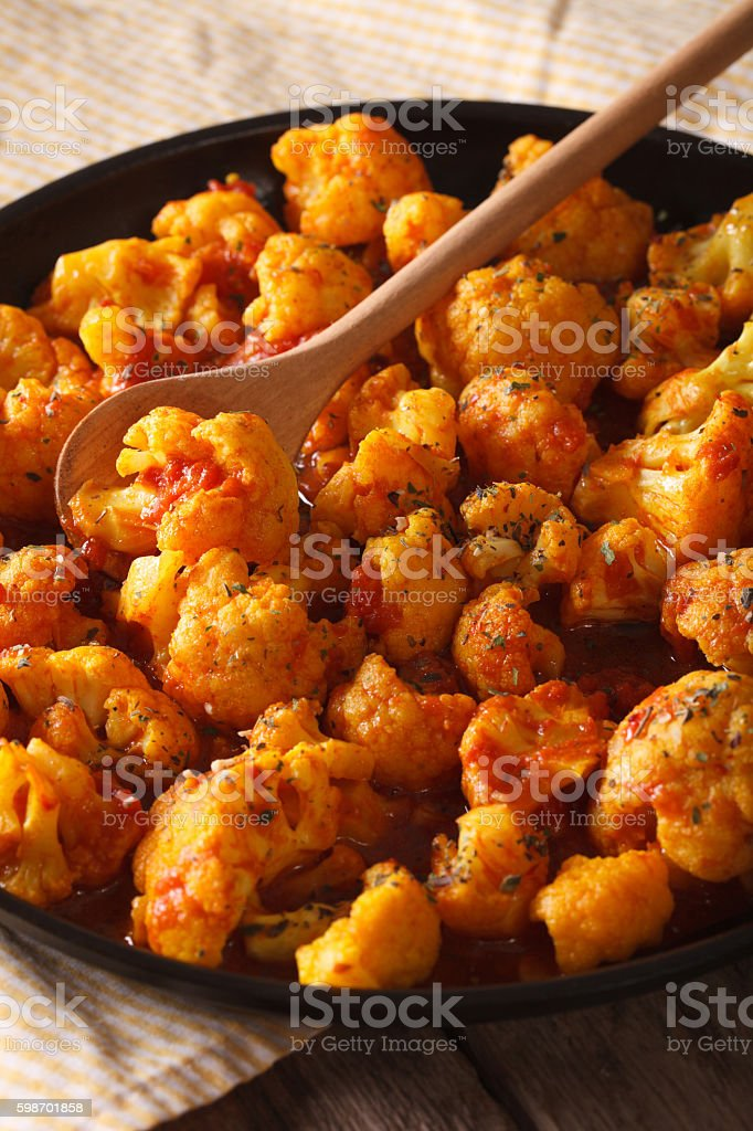 Vegetarian food: Cauliflower in curry sauce close-up. vertical stock photo
