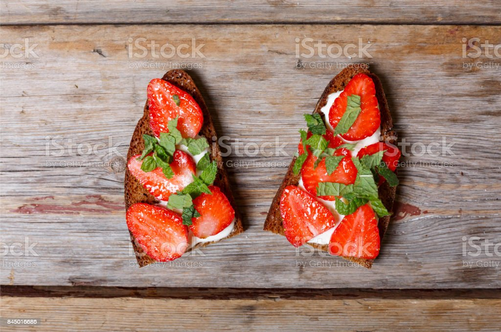 Vegetarian food. Two sandwiches with strawberries, sour cream and mint on a wooden background stock photo