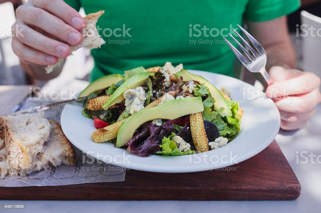 Vegetarian lunch. Man eating salad with avocado and blue cheese. stock photo