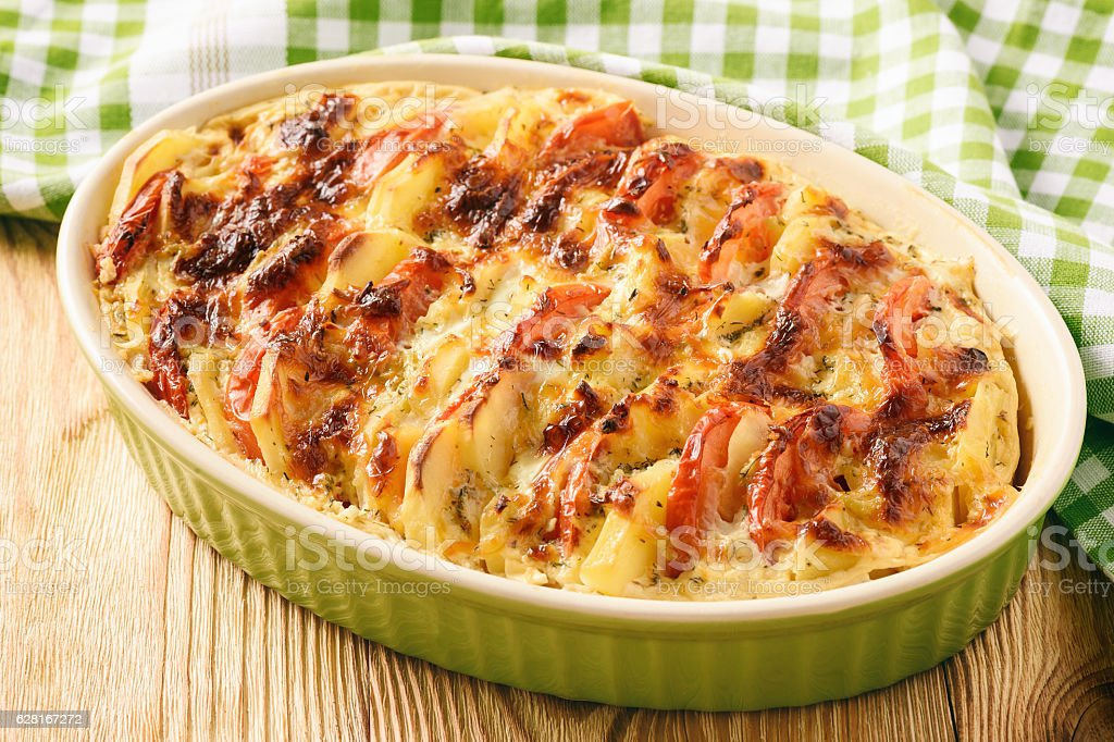 Vegetarian meal - potato casserole with tomatoes, garlic and cheese. stock photo