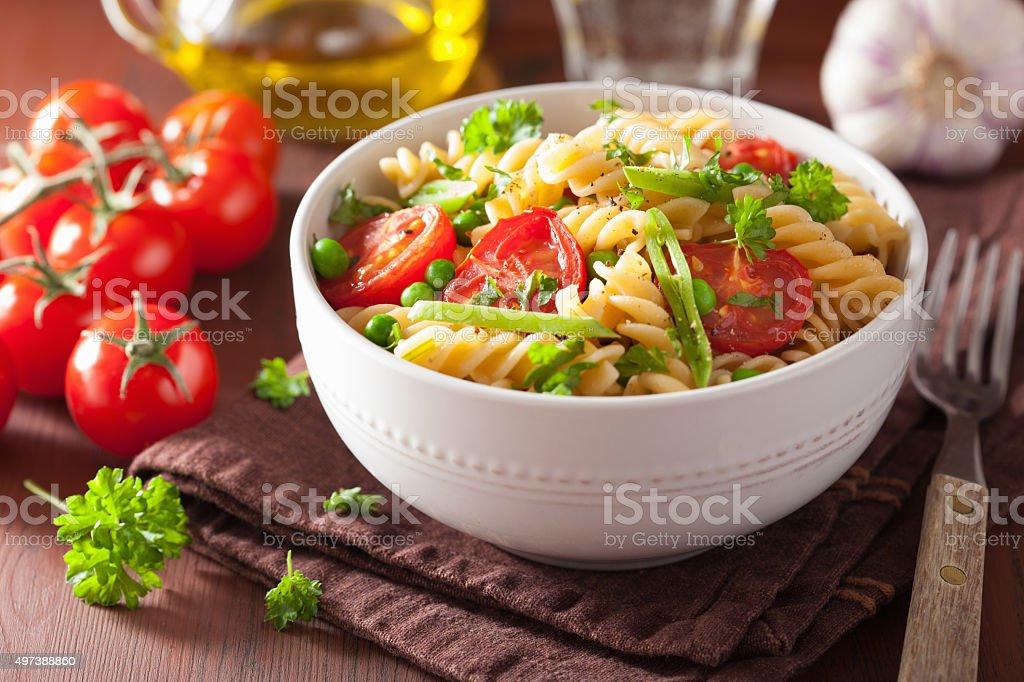 vegetarian pasta fusilli with tomato peas herbs stock photo