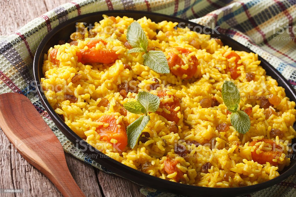 Vegetarian pilaf with saffron and dried fruit close up. horizontal stock photo
