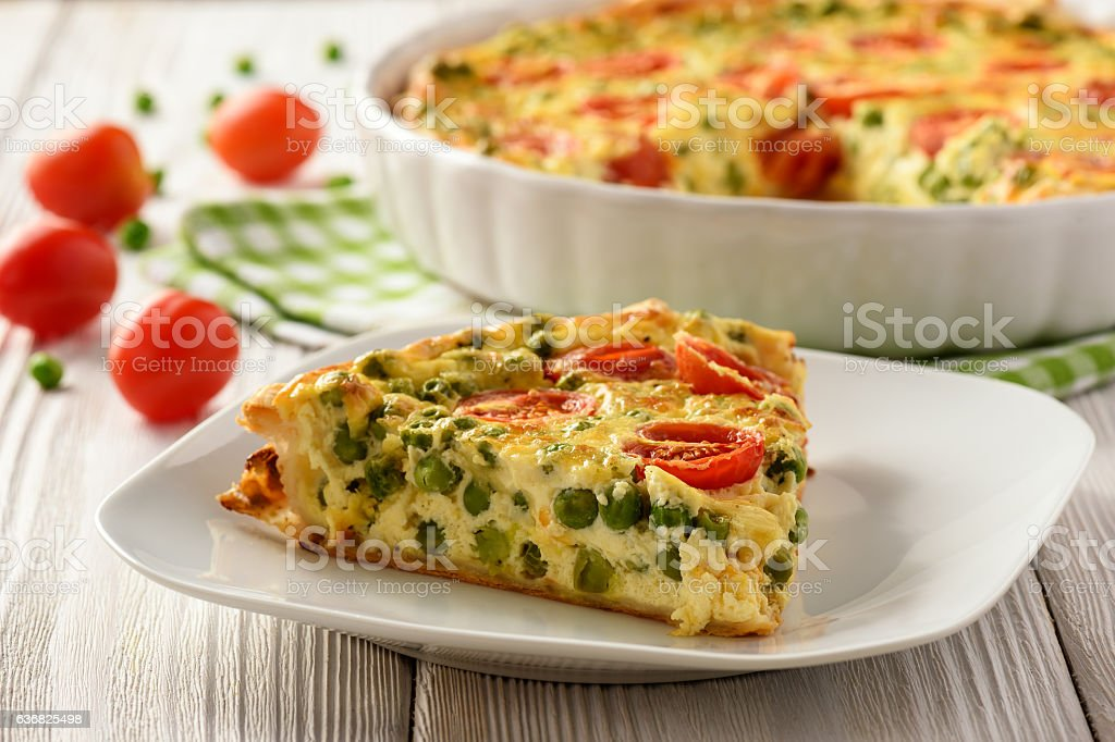 Vegetarian quiche with green pea, tomatoes and cheese. stock photo