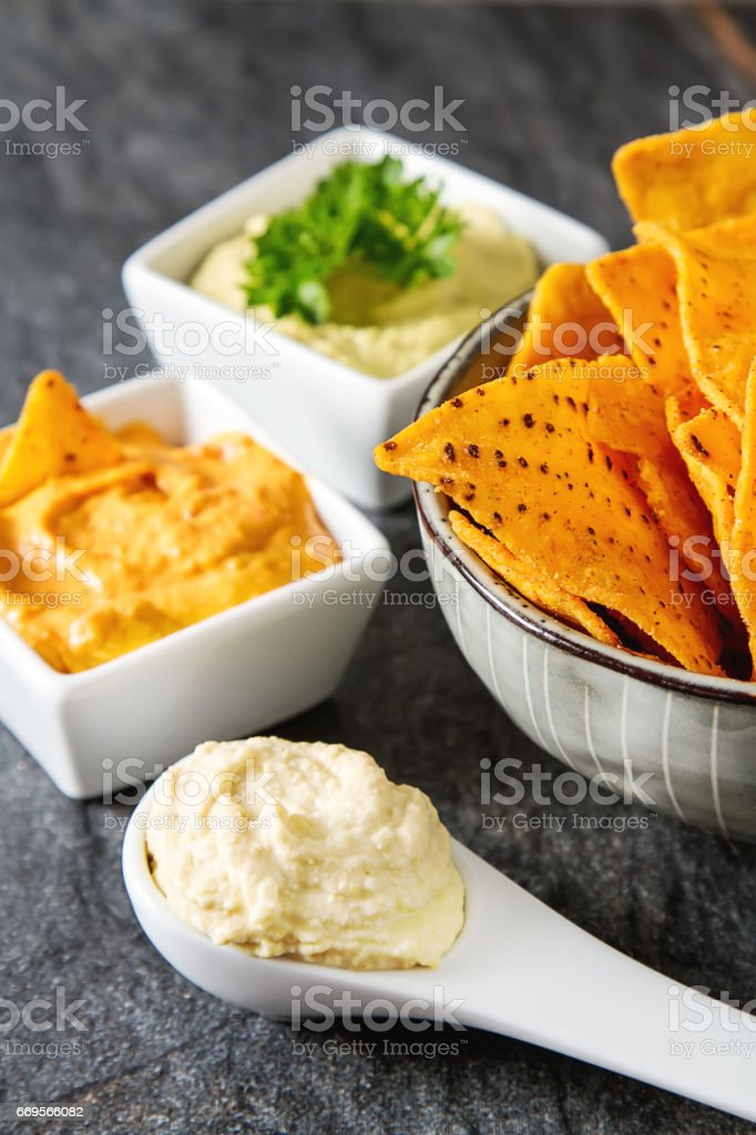 Vegetarian snack. Hummus with greens, dressed with olive oil and paprika in a ceramic plate. Dark background. Traditional Middle Eastern cuisine. Top view. Copy space. Selective focus. The concept of a healthy diet or dietary nutrition. stock photo