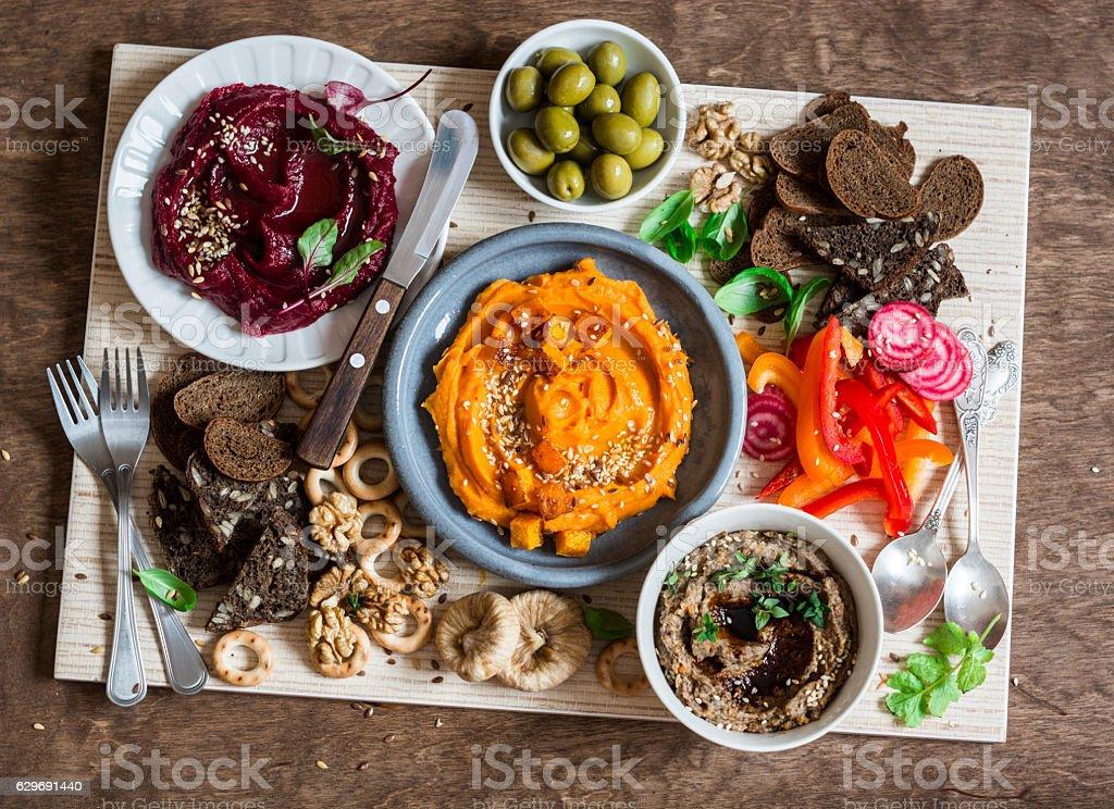 Vegetarian snack table. Pumpkin, beets hummus, mushroom pate, vegetables, bread stock photo