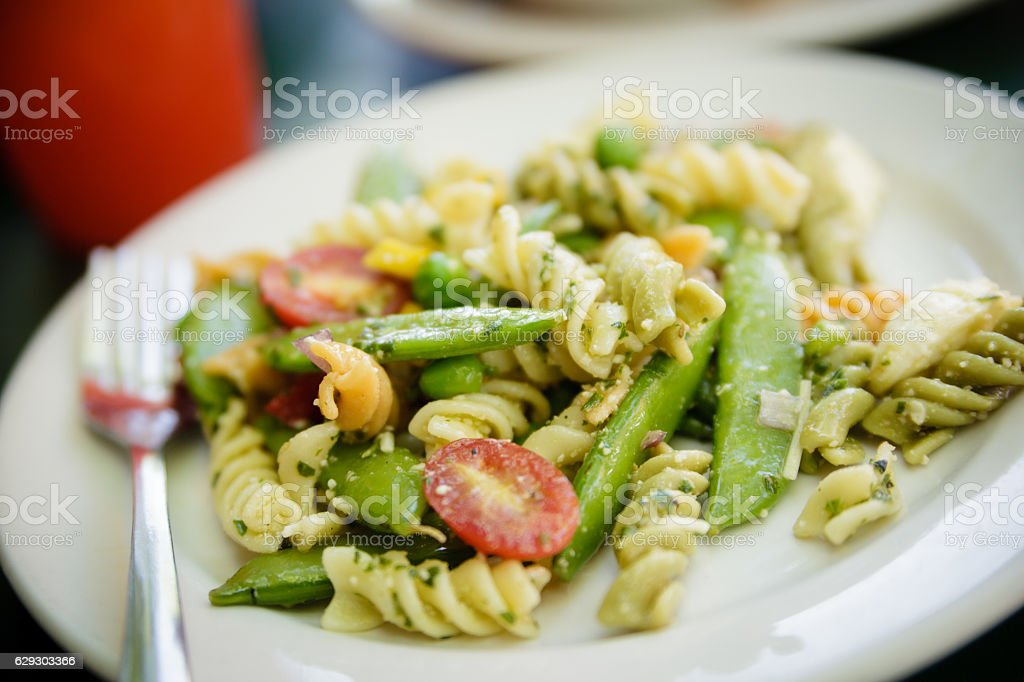 Vegetarian Spinach Rotini pasta with green beans and cherry tomatoes stock photo