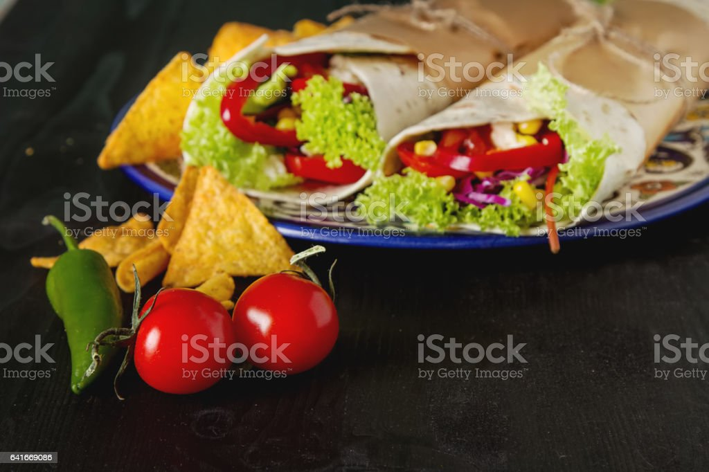Vegetarian tartilla home with tomatoes, cabbage, cheese and salad. Mexican food. Nachos chips. stock photo