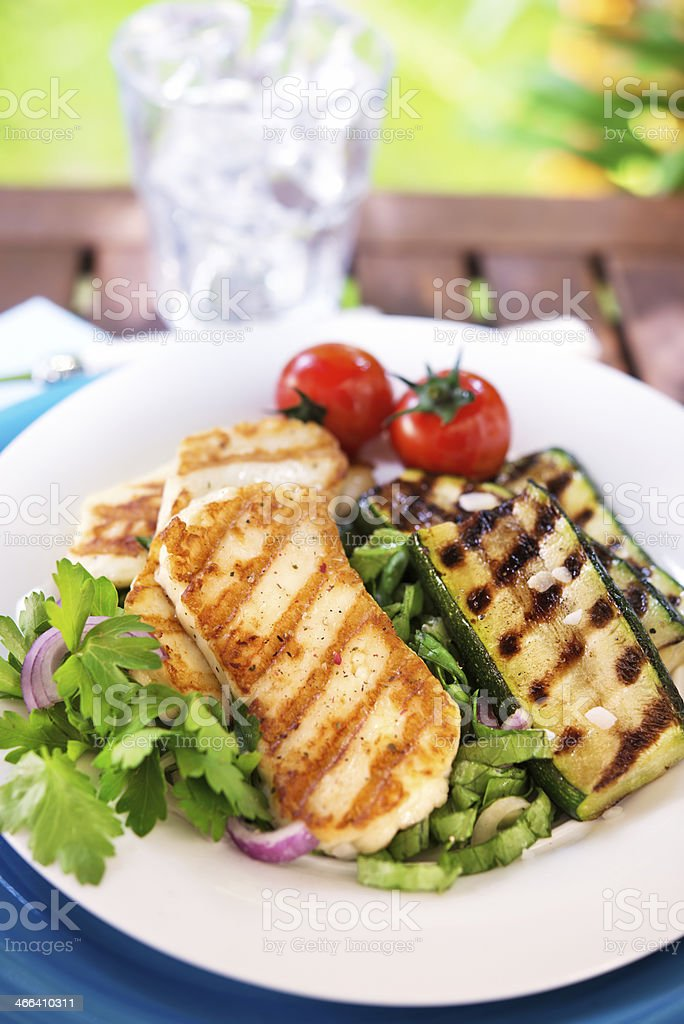 Vegeterian plate with grilled halloumi cheese, zucchini and fresh salad stock photo