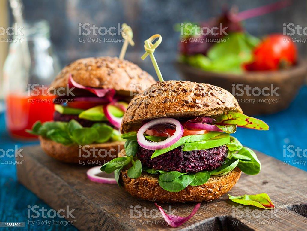 Veggie beet and quinoa burger with avocado stock photo