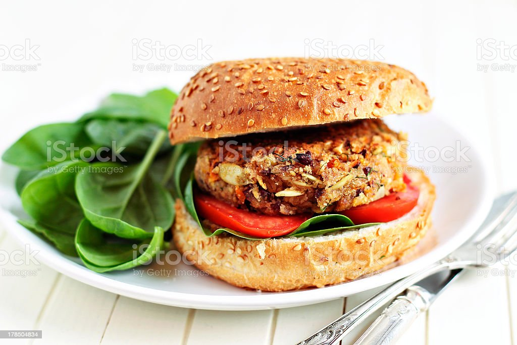 Veggie burger on a white plate with spinach on side stock photo