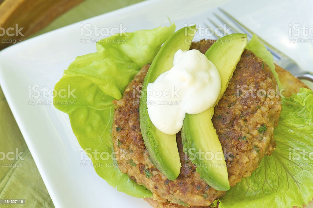 Veggie Burger with Avocado on Lettuce and Bun stock photo