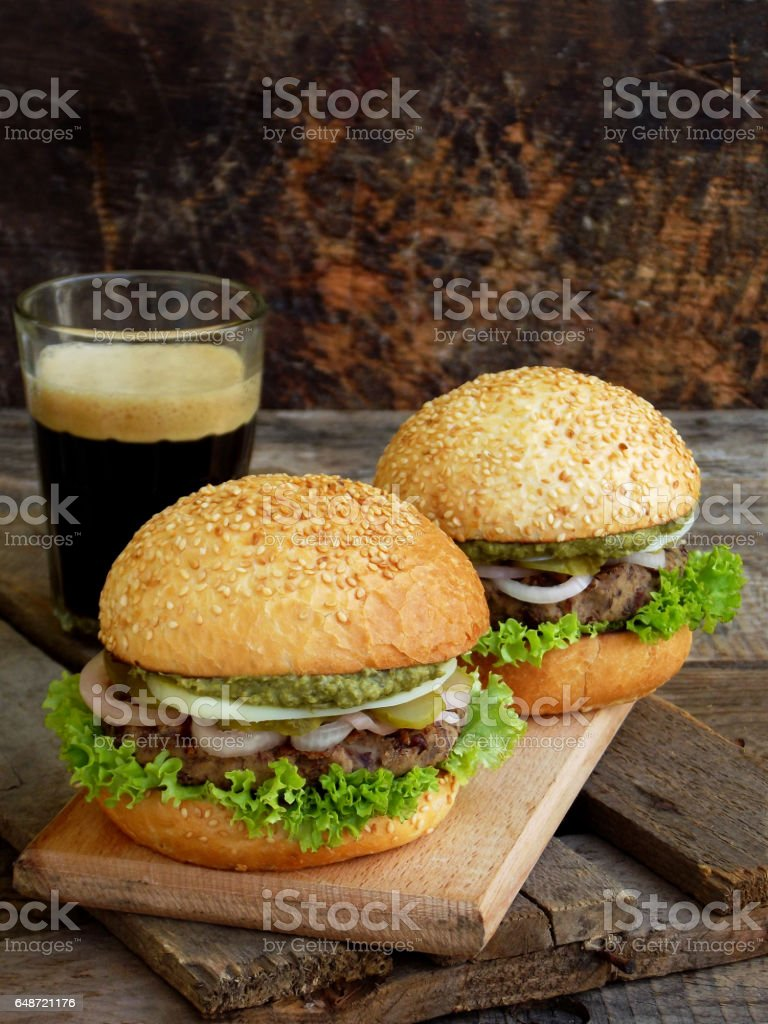 veggie burgers with a chop of black beans, lettuce, pickled onions, cucumber and a glass of dark beer on a wooden background. Space for text stock photo