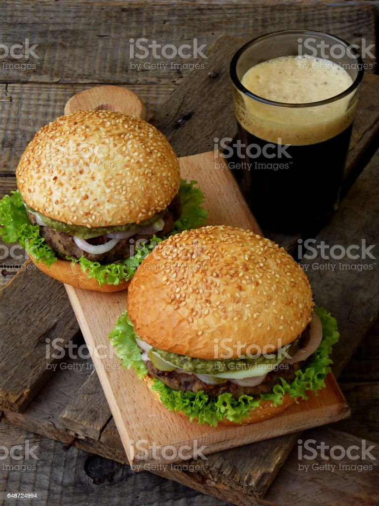 veggie burgers with a chop of black beans, lettuce, pickled onions, cucumber and a glass of dark beer on a wooden background. stock photo