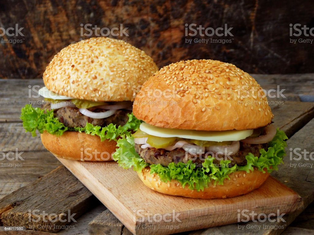 veggie burgers with a chop of black beans, lettuce, pickled onions, cucumber on a wooden background. stock photo