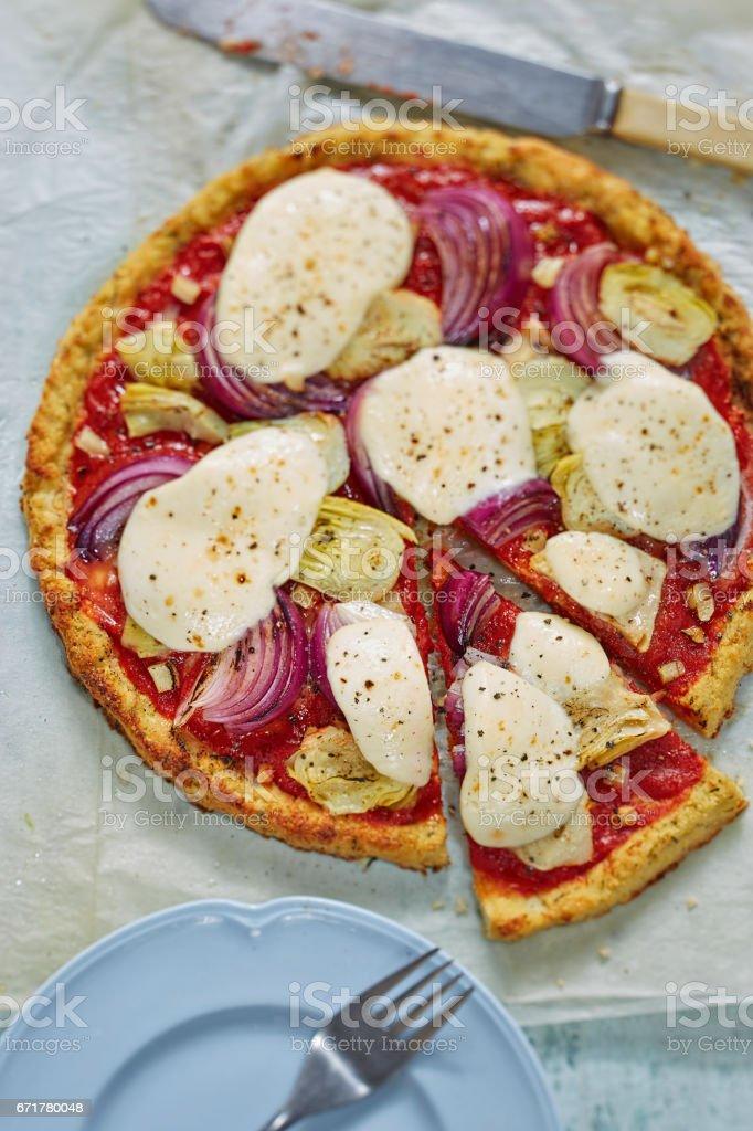 Vegie cauliflower pizza base with artichoke, red onion and mozzarella stock photo
