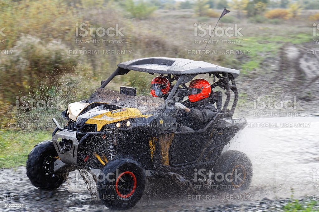 ATV vehicle boosts water hurdle surrounded by splashes. stock photo