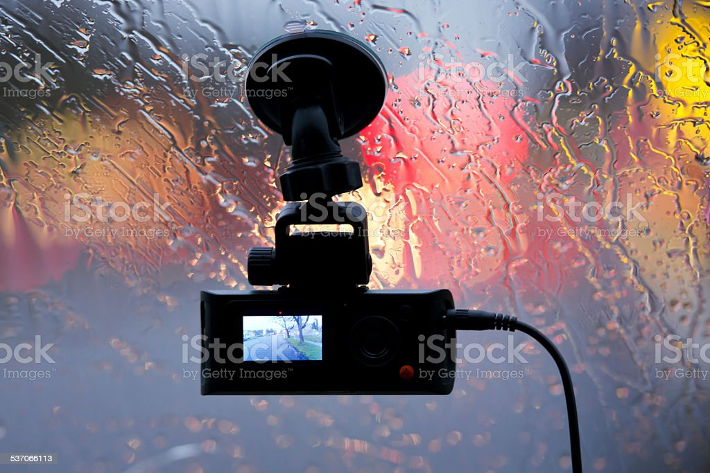 Vehicle DVR on glass of car in rain lights reflection stock photo