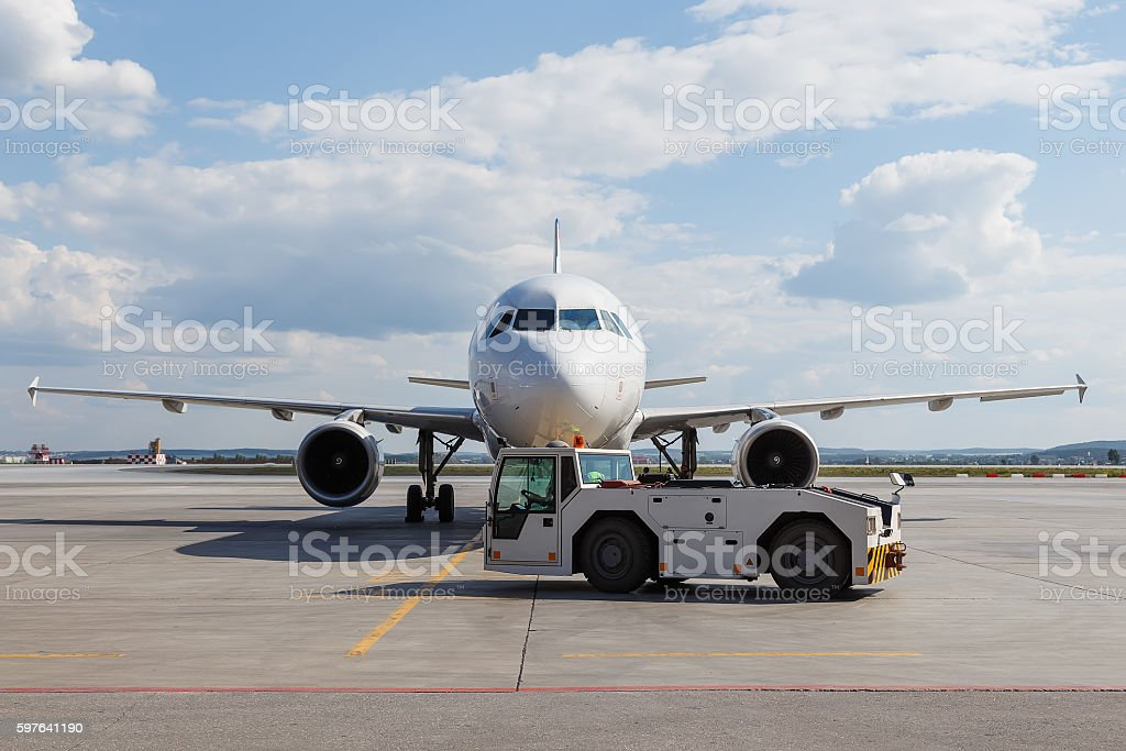 Vehicles towing white modern aircraft on parking lot stock photo