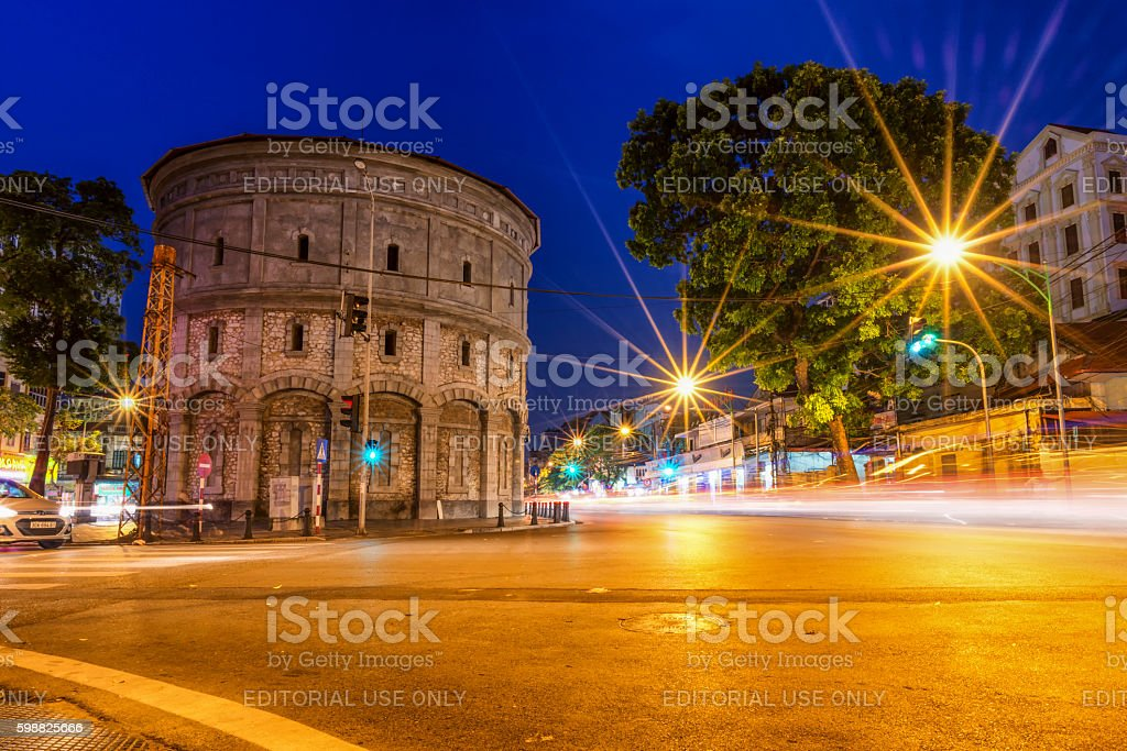 Vehicles traveling in front of Hang Dau water tower. stock photo