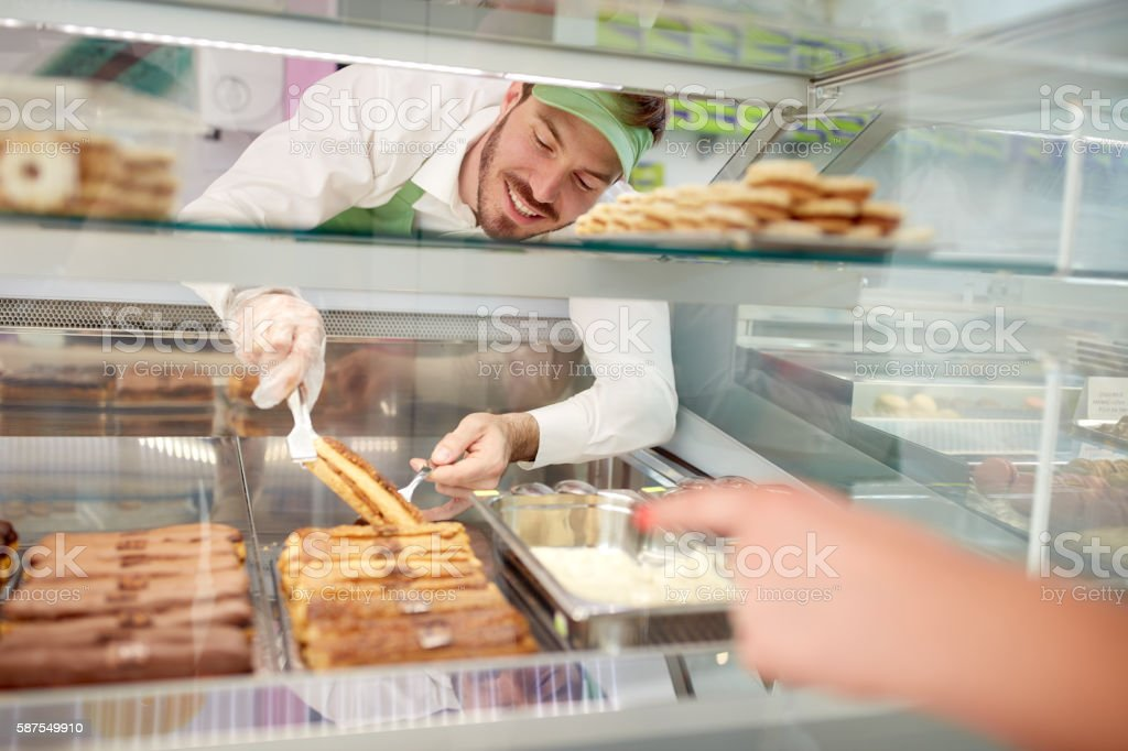 Vendor in bakery taking out biscuit with cream from showcase stock photo
