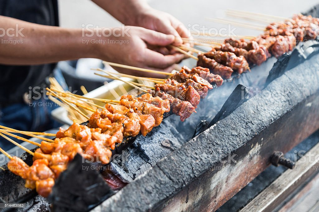 Vendor preparing chicken and beef barbecue satay on charcoal gri stock photo