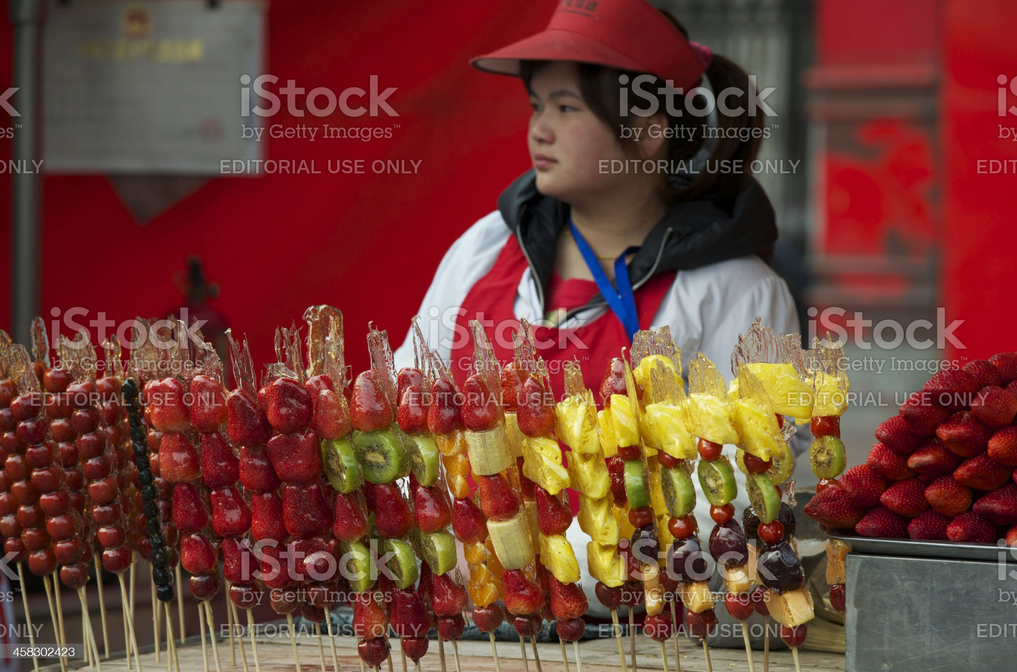 Vendor selling sugar-coated fruits on sticks at Beijing snack street royalty-free stock photo