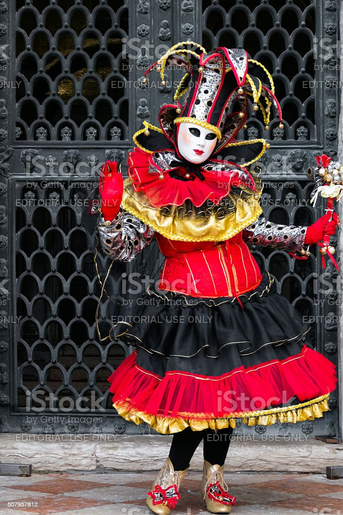 Venetian carnival costume in front of metal gate stock photo