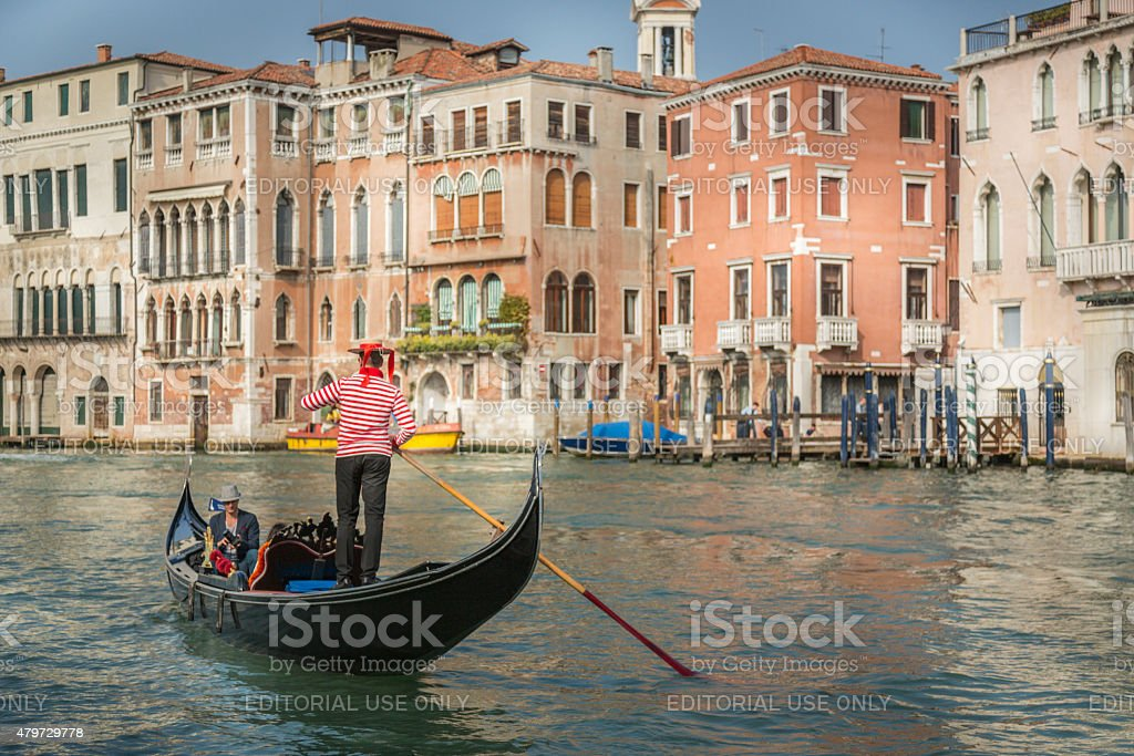 Venetian gondolas with tourists sail in the canal in Venice stock photo