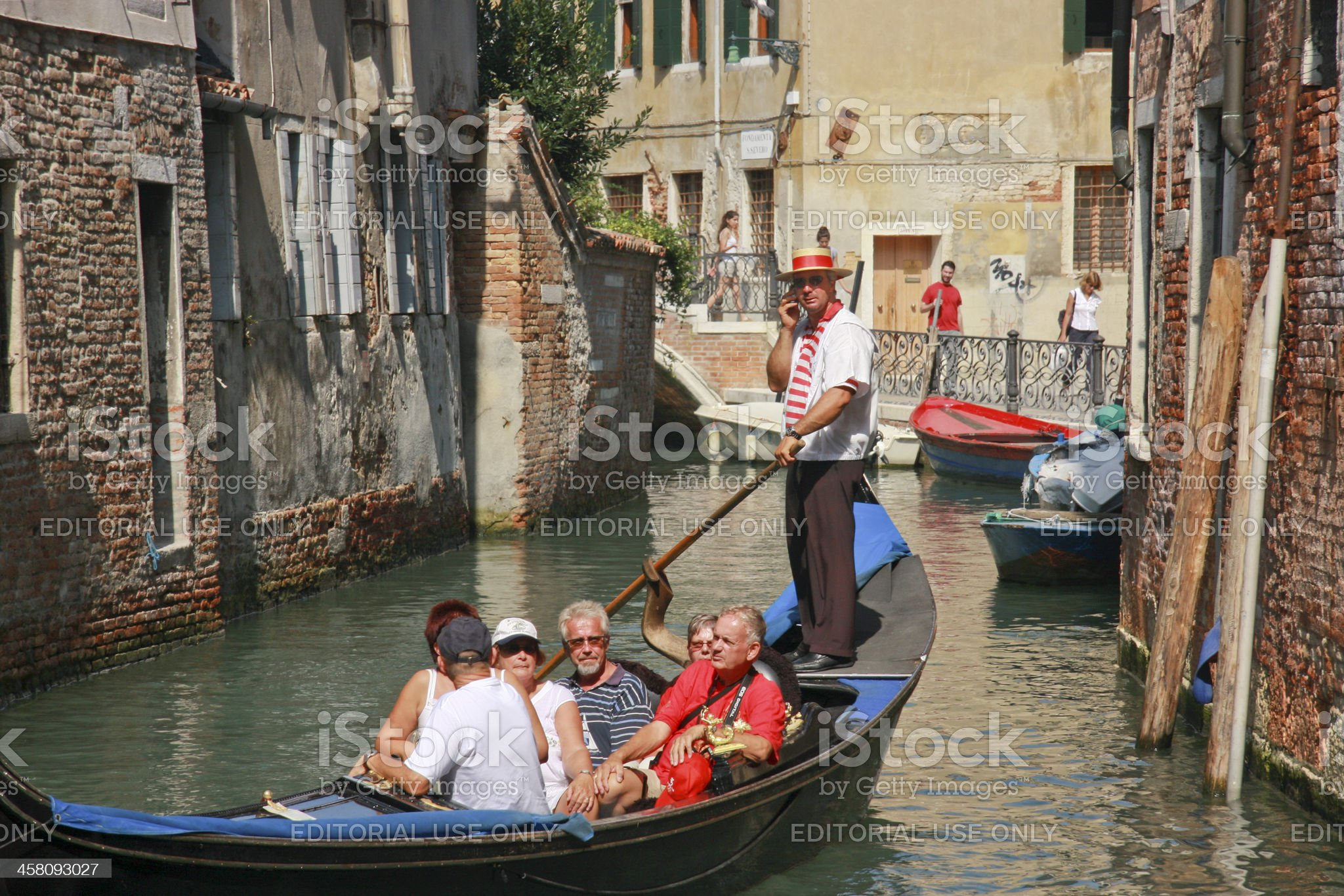Venetian gondolier rowing gondola speaking to somebody by cellphone royalty-free stock photo