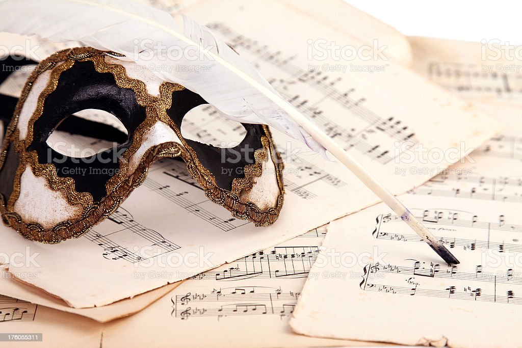 Venetian mask, notes and feather. royalty-free stock photo