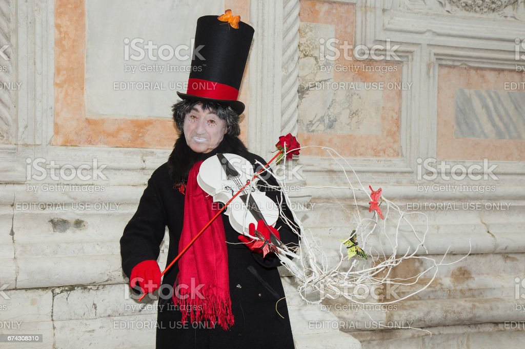 Venetian Mask of Male Pierrot playing white violin with red rose on San Zaccaria Square - Venice Carnival stock photo