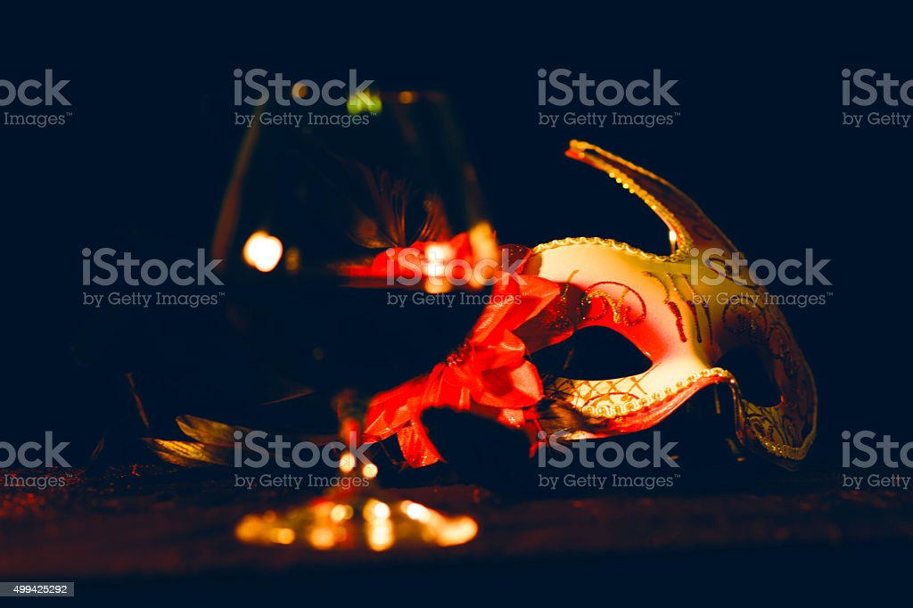 Venetian mask with glass of wine on a table. stock photo