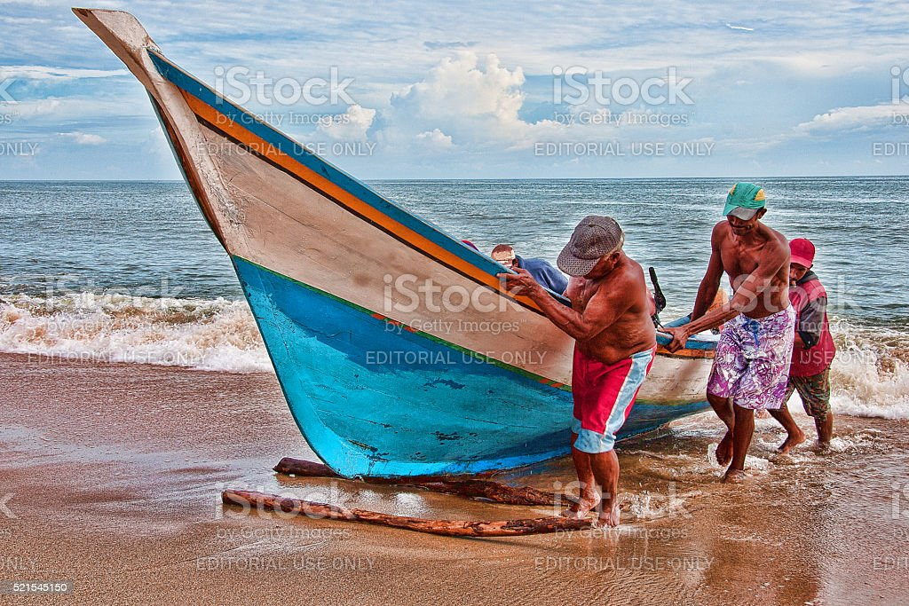 Venezuelan fishermen working together to drag a fishing boat to shore stock photo