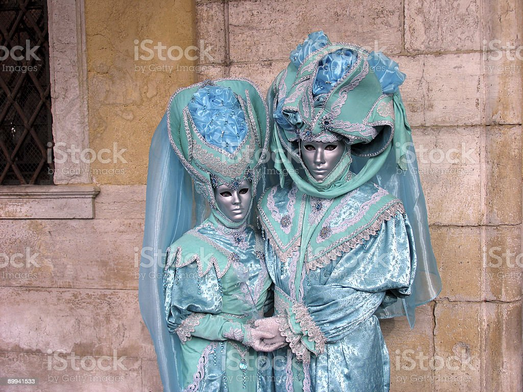 Venice Carnival: Couple in turquoise costumes, holding hands royalty-free stock photo