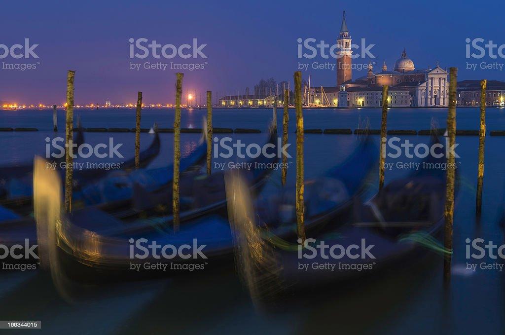 Venice gondolas rocking on Grand Canal below illuminated campanile Italy royalty-free stock photo