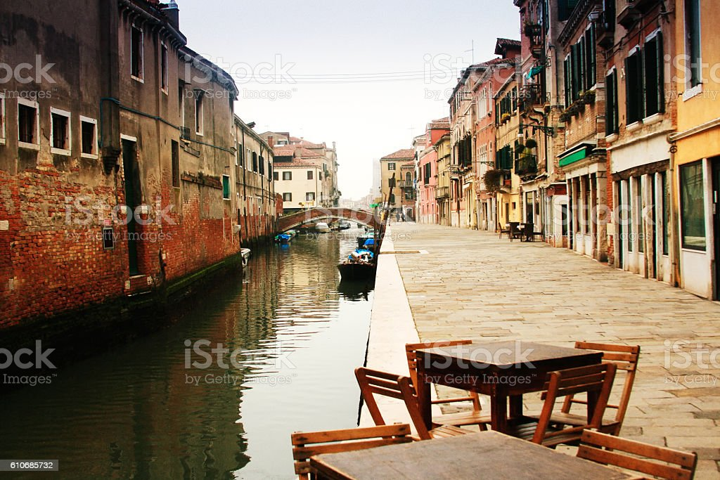 Venice, Italy: Wooden Cafe Tables Along Quiet Small Canal stock photo