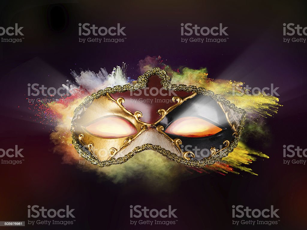 Venice mask with colored powder and glowing eyes stock photo