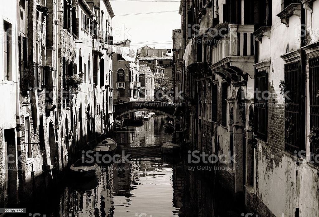 Venice narrow dark canal Italy Black and White water house stock photo