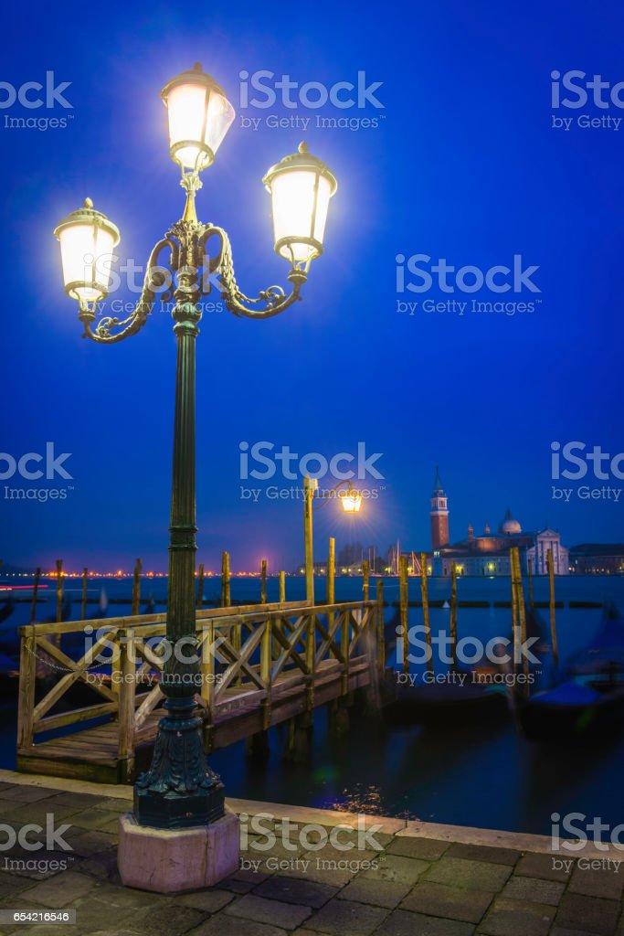 Venice warm lamplight on gondolas St Mark's Square night Italy stock photo