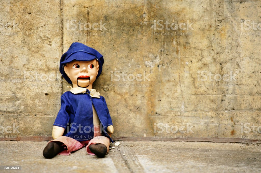 Ventriloquist Dummy Sitting Against Concrete Wall stock photo