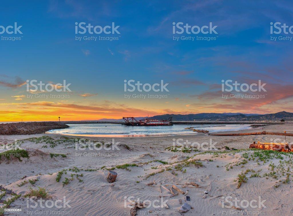 Ventura Harbor dredge barge at sunset. stock photo