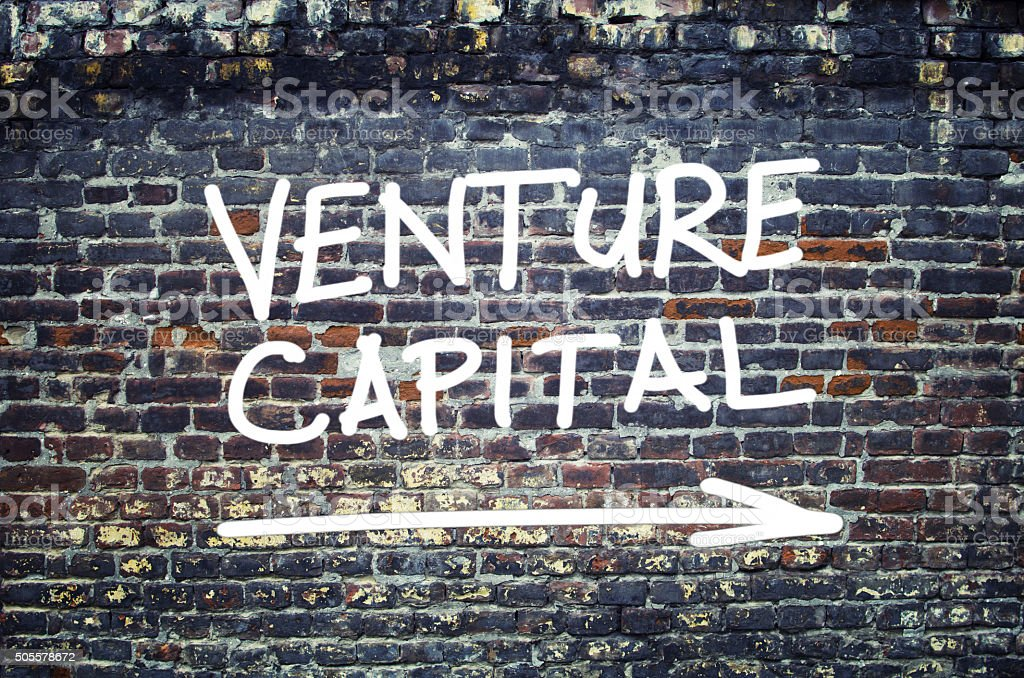 Venture capital text on brick wall stock photo
