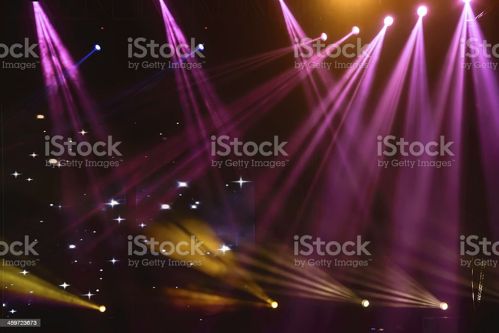 Venue stage with purple and gold spotlights flashing stock photo