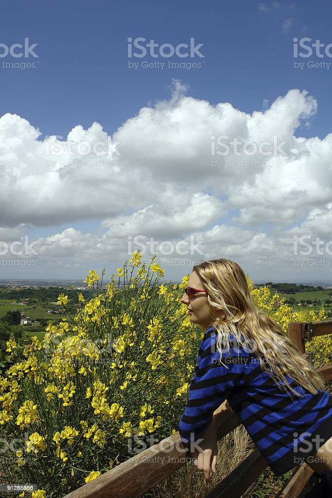Vernal relax; blond woman,flowers, white clouds stock photo