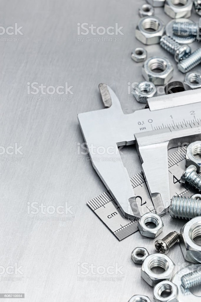 vernier caliper, standard ruler, screws and bolts on scratched metal stock photo