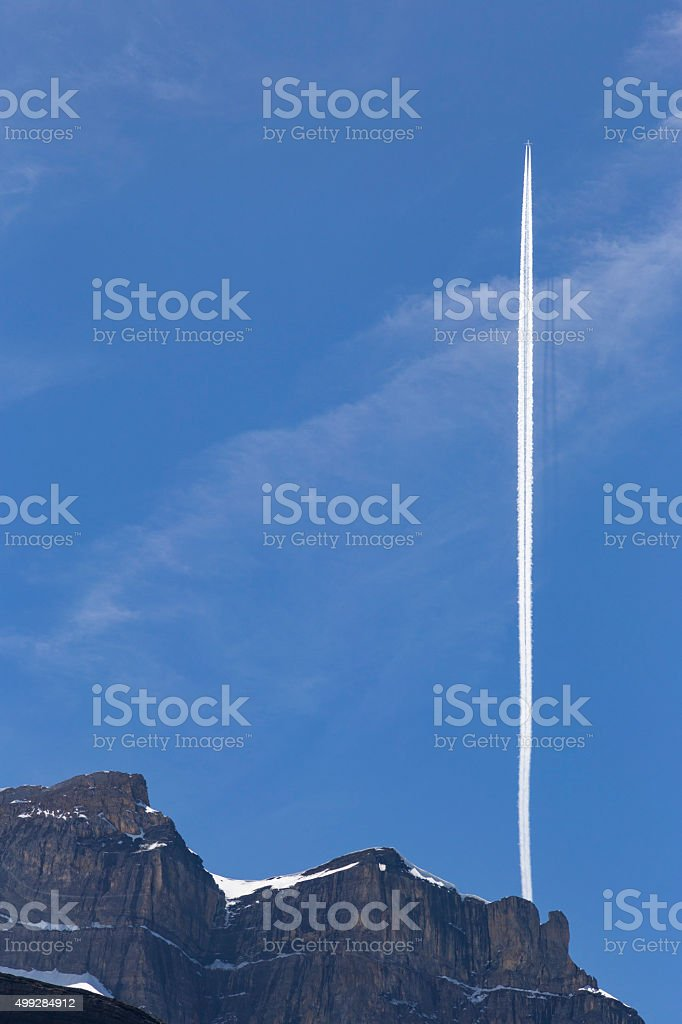 Vertical contrail of airplane over snowy mountain peak, Switzerland stock photo