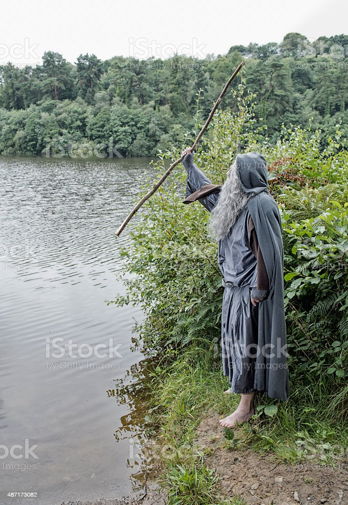 Vertical image of a wizard over looking a lake stock photo