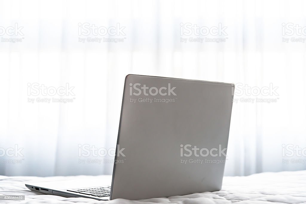 Vertical image of laptop in bed. stock photo